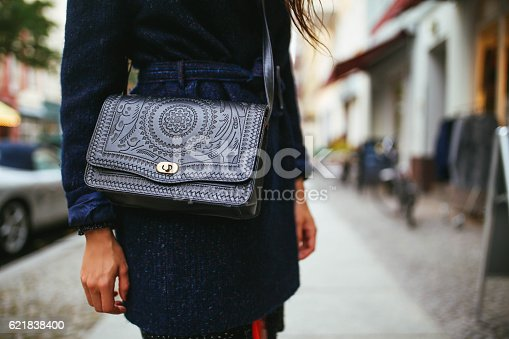 Close up on the young woman's purse and a dark coat on the streets of Berlin, in Kreuzberg - Schoneberg district. Vintage color graded, shot with large aperture lens for smooth and creamy bokeh background.