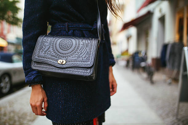 young woman street style leather purse and a coat - street style stockfoto's en -beelden