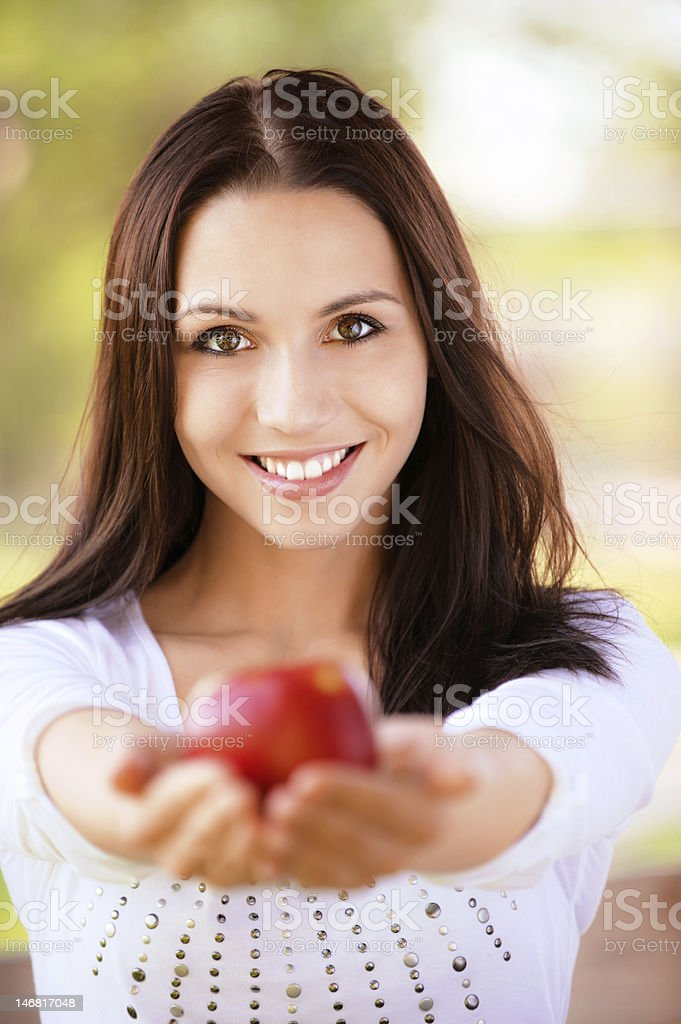 Young woman stretches apple royalty-free stock photo