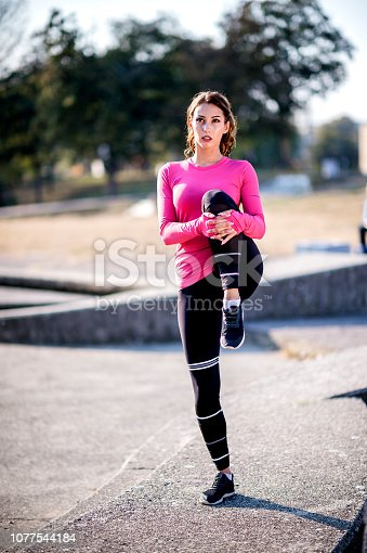 istock Young  woman stretching after training 1077544184