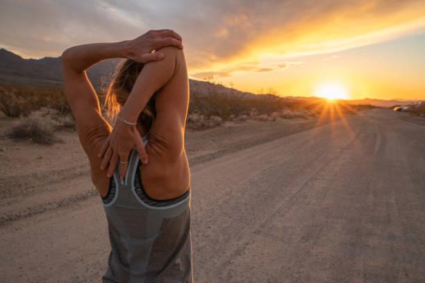Junge Frau streckt Körper nach dem Joggen, Sonnenuntergang am Ende der Straße; Weibchen dehnt Körper in der Natur – Foto