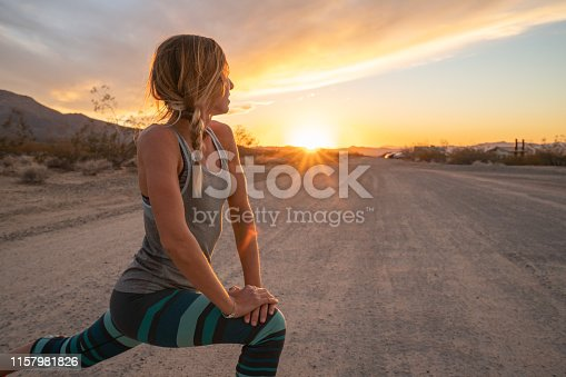 Young woman stretching body after jogging, sunset at the end of the road; female stretches body in nature  USA
