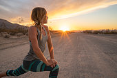 Young woman stretching body after jogging, sunset at the end of the road; female stretches body in nature \nUSA