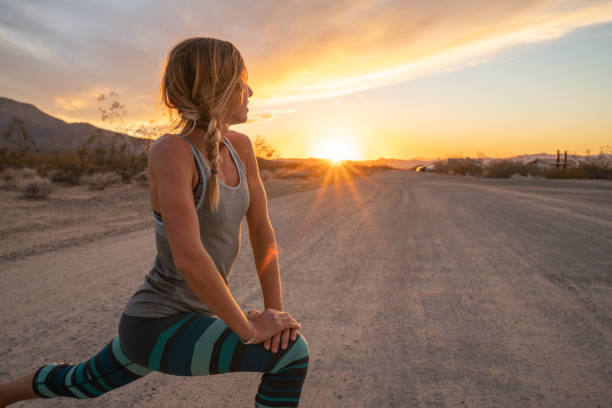 Young woman stretching body after jogging, sunset at the end of the road; female stretches body in nature stock photo