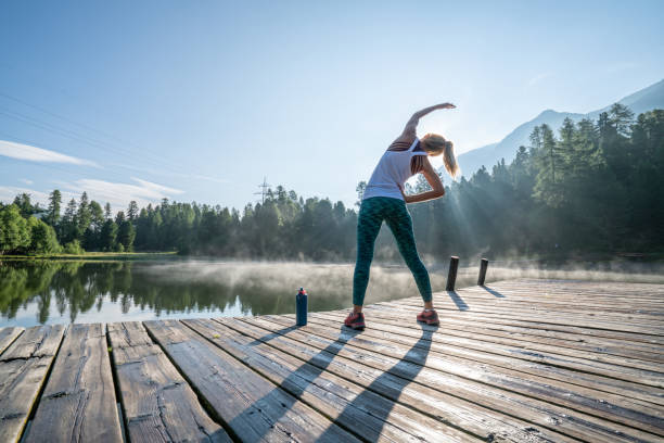 Young woman stretching body on morning jogging, sunrise over beautiful peaceful lake in nature, female standing on pier over water stock photo