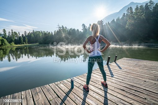istock Young woman stretching body on morning jogging, sunrise over beautiful peaceful lake in nature, female standing on pier over water 1090258572