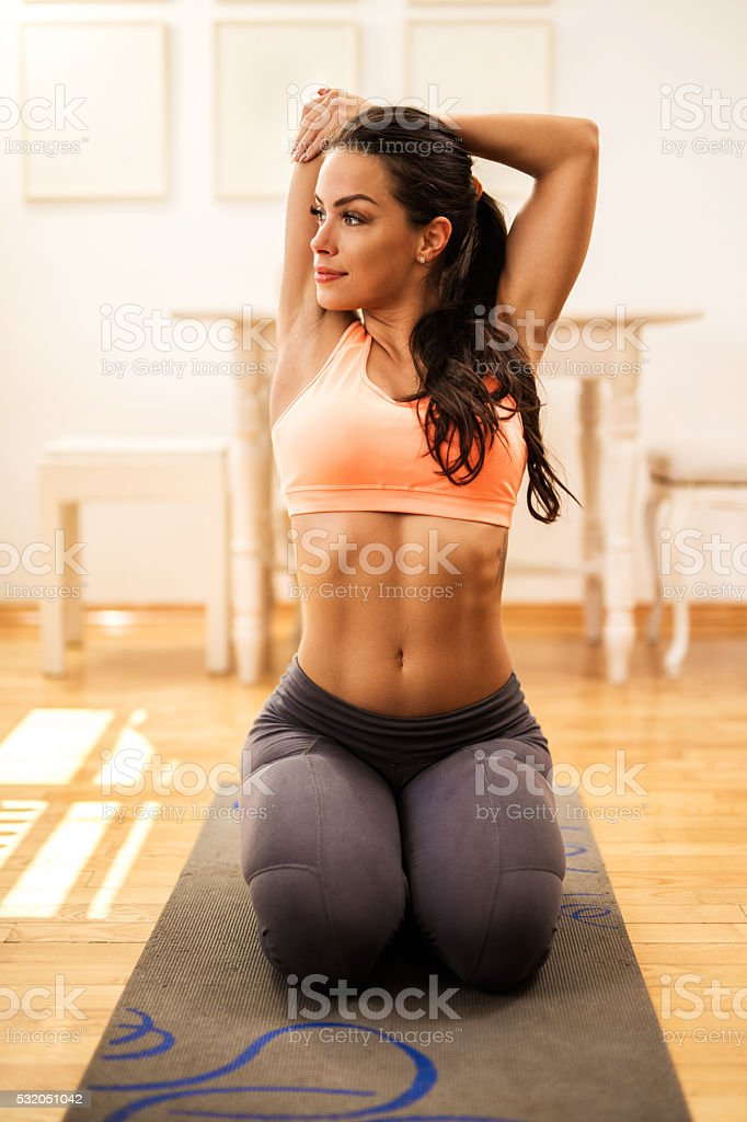 Young woman stretching her arms before sports training at home. stock photo