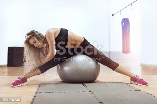istock Young Woman Stretching in Gym Training with Exercise Ball 599470206