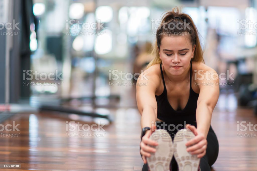 Young woman stretching in the gym stock photo