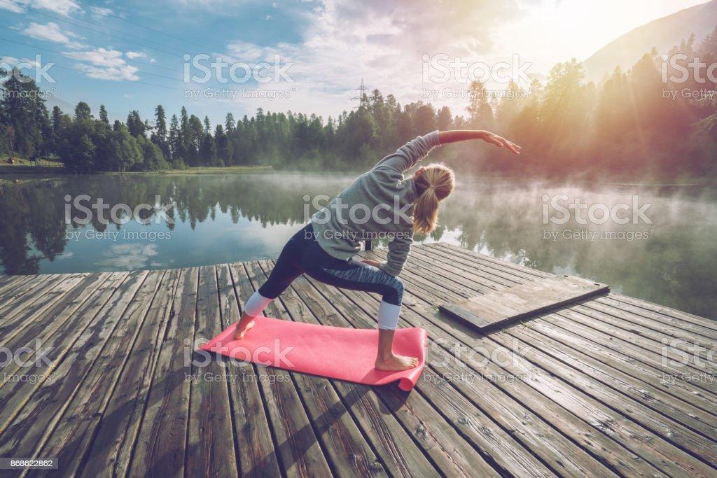 Junge Frau, die Dehnung in der früh, Yoga am See - Lizenzfrei Aktiver Lebensstil Stock-Foto