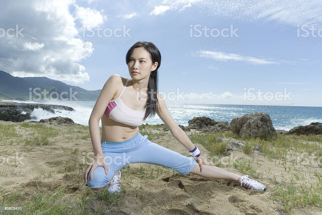 Young woman stretching legs on beach royalty-free stock photo