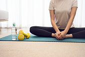 istock Young woman stretching on a yoga mat to relax 1335210458