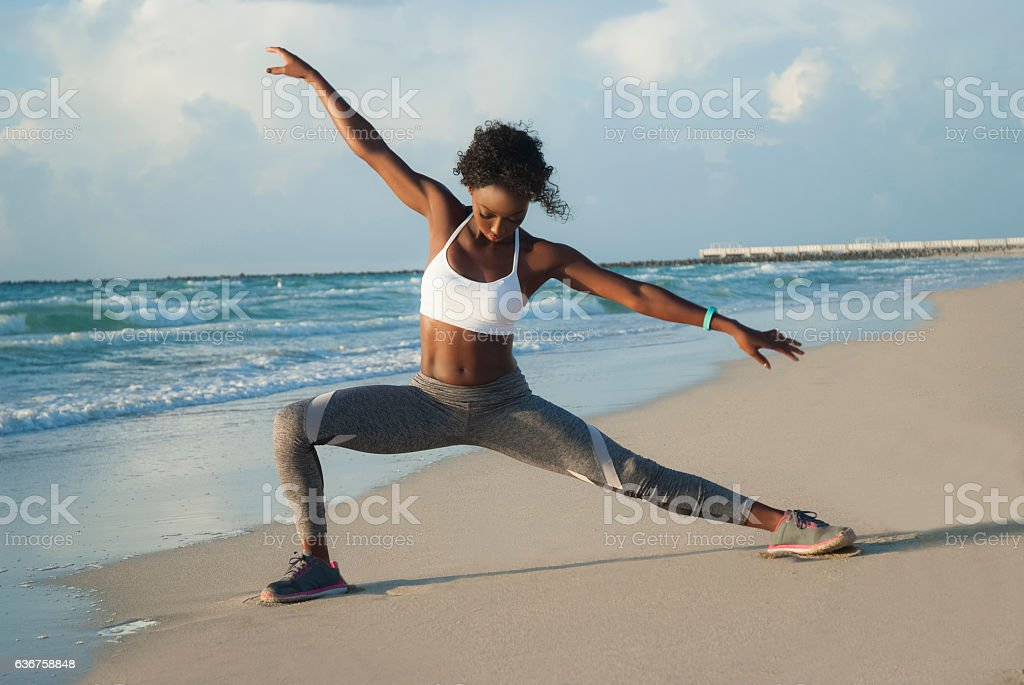Young woman stretching on beach stock photo