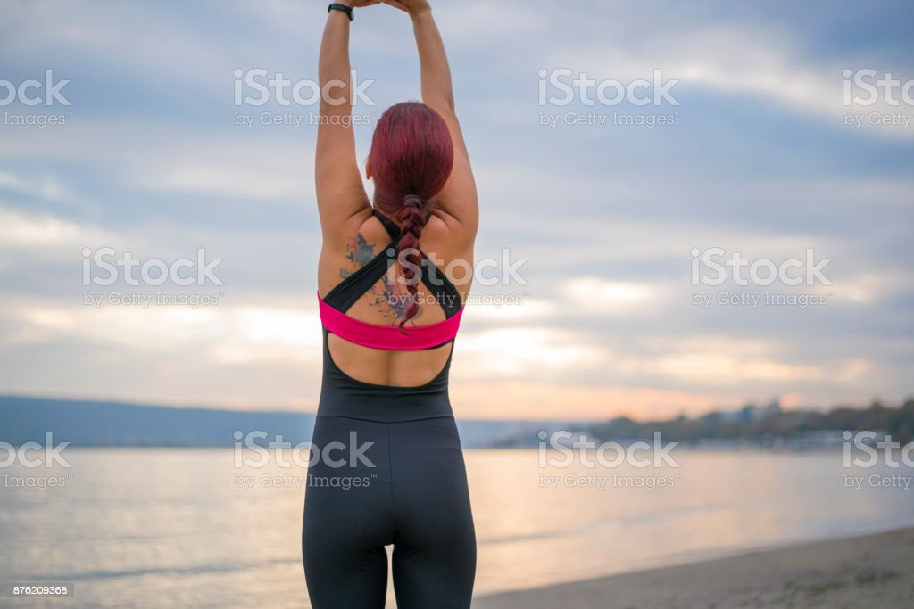 Young woman stretching on the beach - close-up stock photo