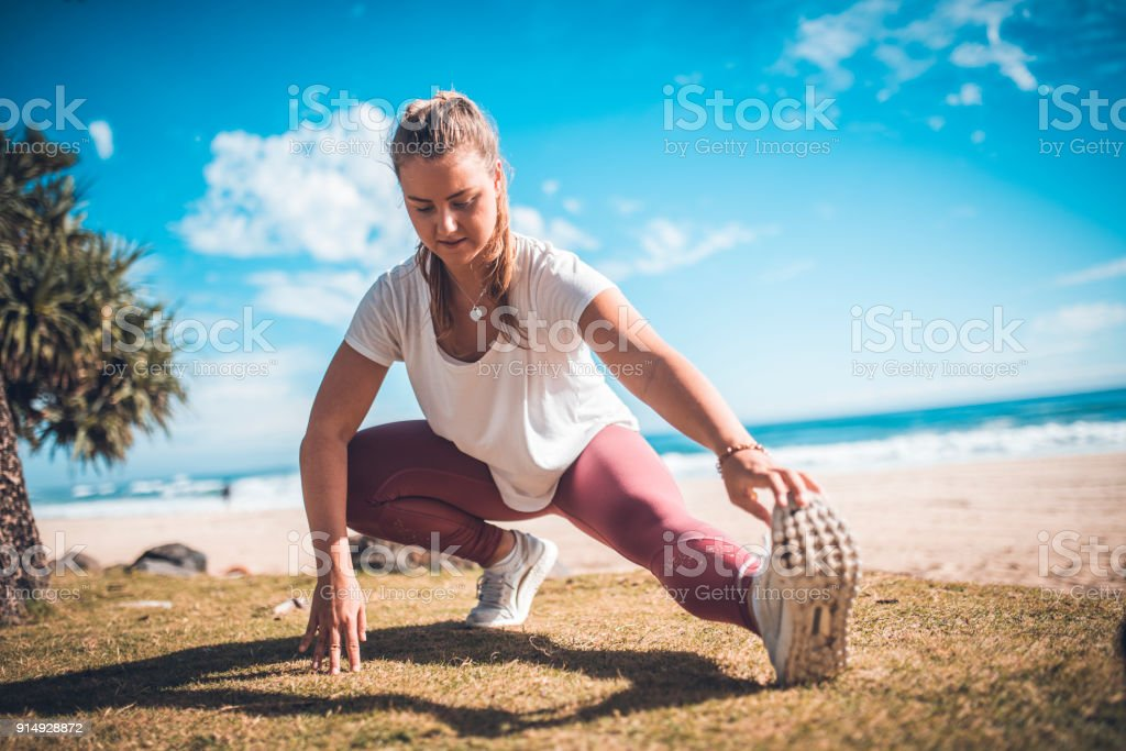 Young woman stretching on the beach stock photo