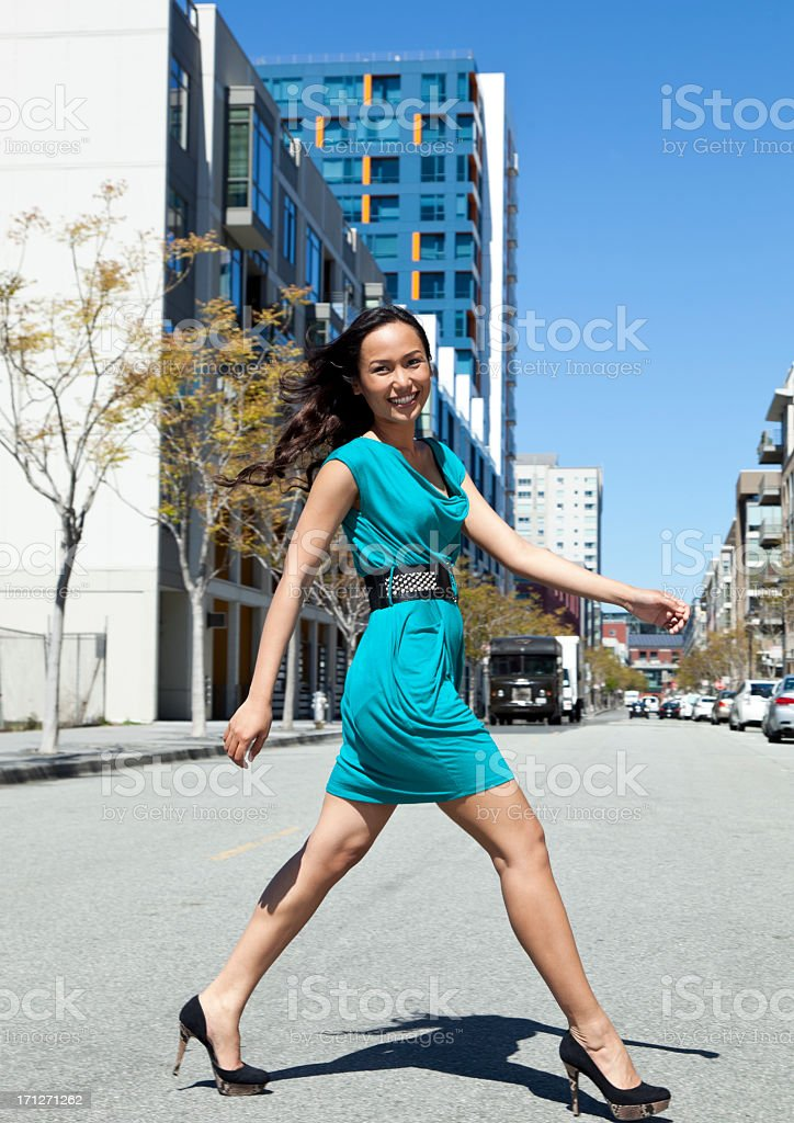 young woman striding across the street stock photo