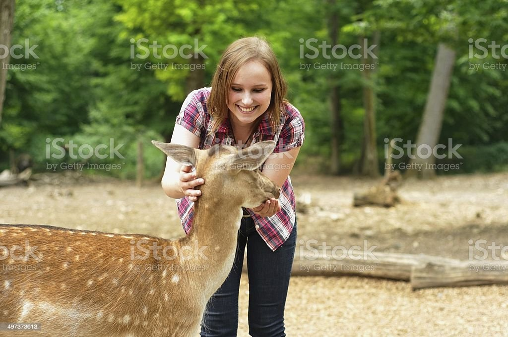 Young woman stroking a deer royalty-free stock photo