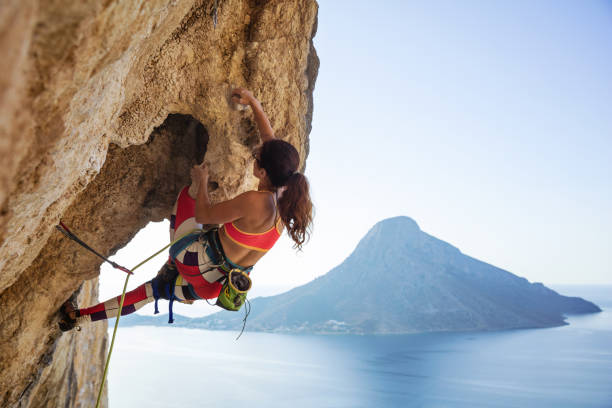 Young woman struggling to climb ledge on cliff stock photo