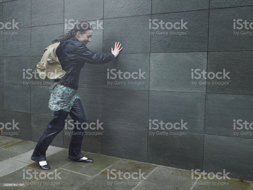Young woman struggling to walk in rainstorm, eyes closed stock photo