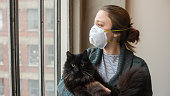 Young woman looks out her downtown apartment window holding her cat. Los Angeles is under shelter-in-place orders due to the Coronavirus pandemic of 2020.
