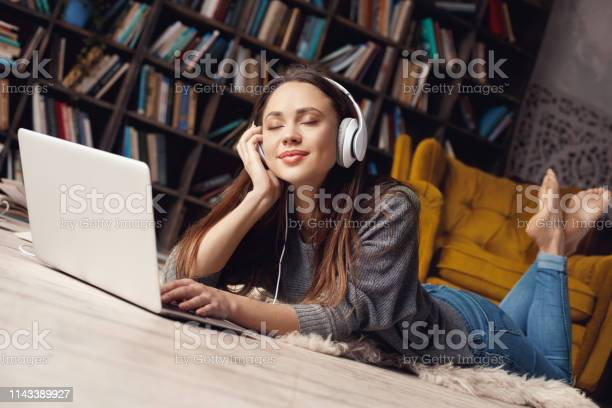 Young woman student in library at home lying listening favorite song picture id1143389927?b=1&k=6&m=1143389927&s=612x612&h=9xvuo83goxp d5 xgyoq9ir2ibl7prwjo6gwykxzrka=