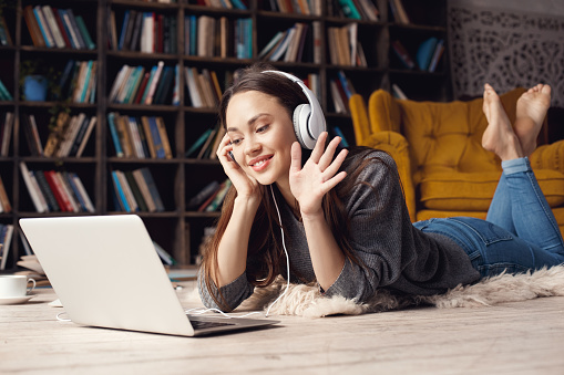 istock Young woman student in library at home lying video call 1143611549
