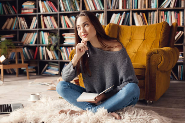 Young woman student in library at home sitting looking up dreaming stock photo