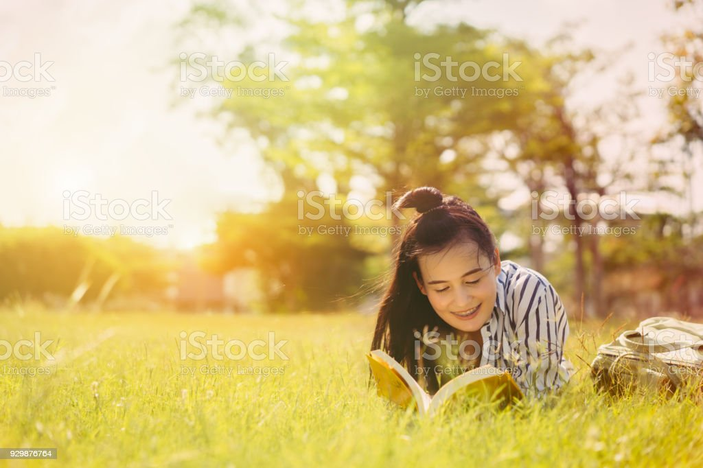 Young woman student reading book in university campus college and serious study learning knowledge at park outdoor stock photo