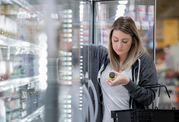 Young woman studies nutrition label of almond milk while shopping in grocery store stock photo