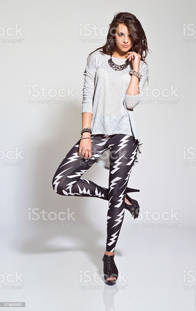 Young Woman, Studio Portrait Full lenght portrait of contemporary young woman wearing rock style clothes, looking at the camera. Studio shot, white background. 20-24 Years Stock Photo