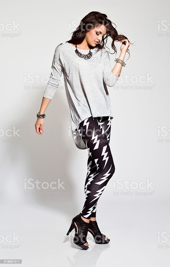 Young Woman, Studio Portrait Full lenght portrait of contemporary young woman wearing rock style clothes. Studio shot, white background. 20-24 Years Stock Photo