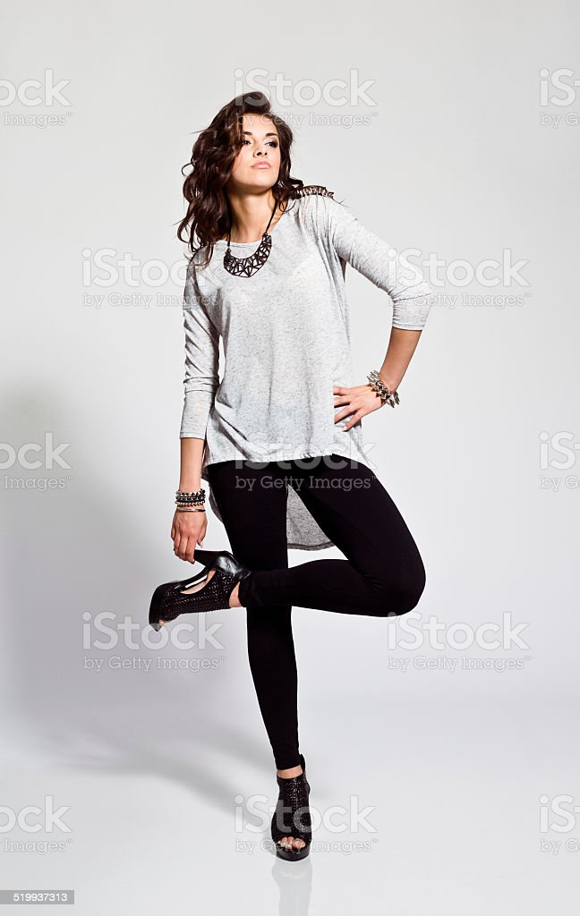 Young Woman, Studio Portrait Full lenght portrait of contemporary young woman wearing rock style clothes and high heels. Studio shot, white background. 20-24 Years Stock Photo