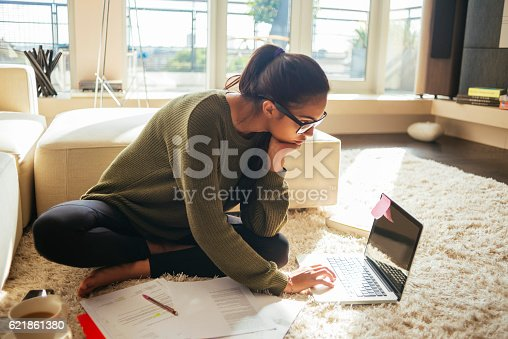 young woman studying and working on her laptop,sitting on the carpet in the living room,nice sunny day