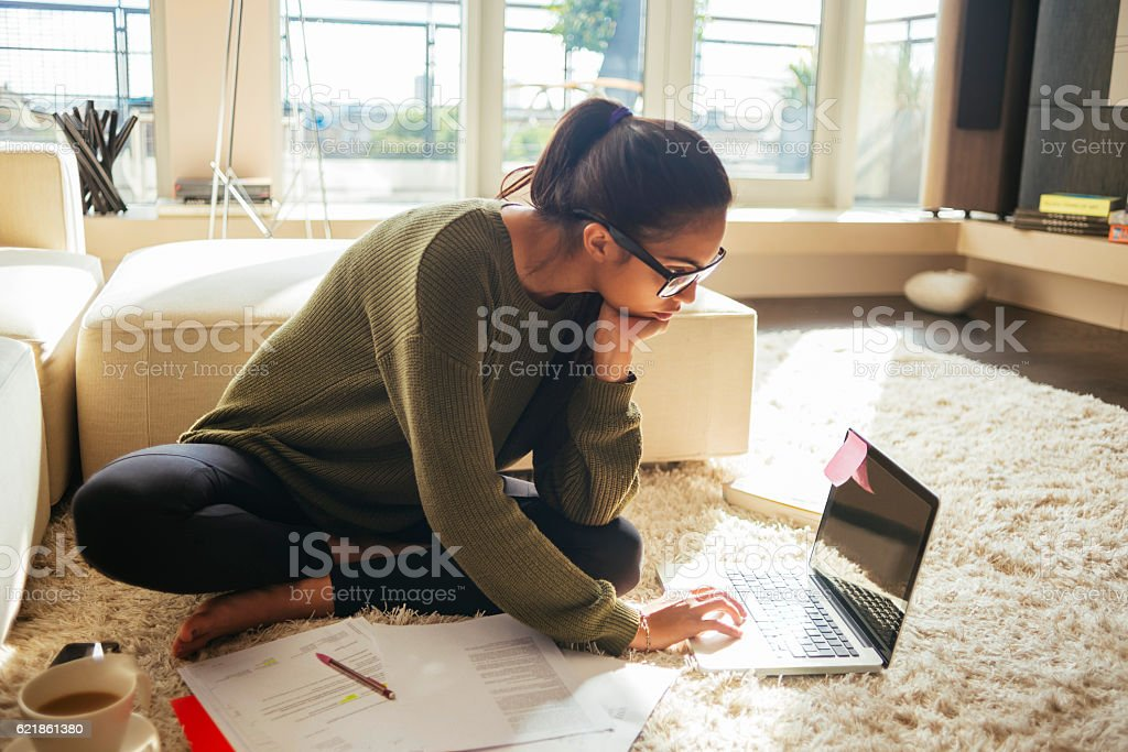 young woman studying and working on her laptop stock photo