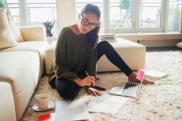 young woman studying in her living room - writing class stock photos and pictures