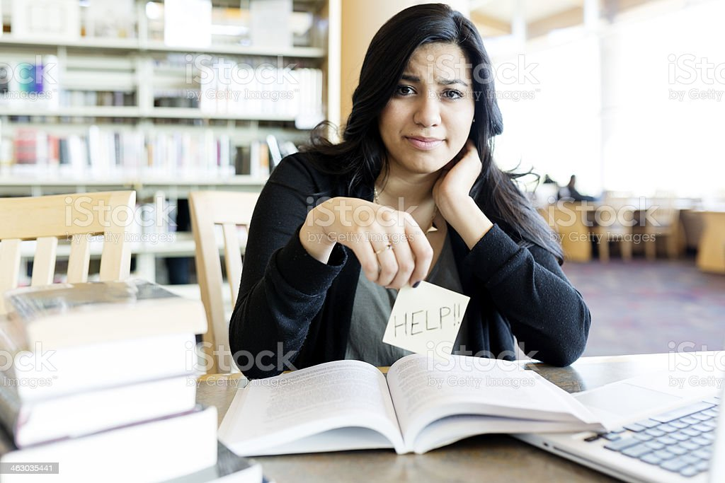 Young woman studying in library frustrated. stock photo