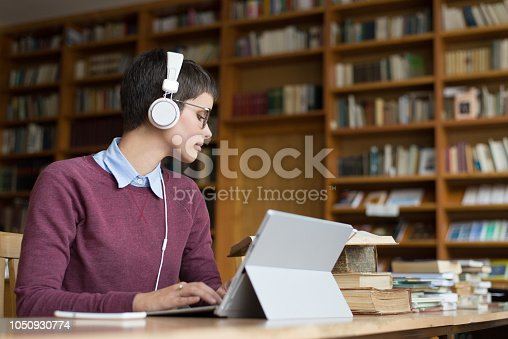 istock Young woman studying in the library 1050930774