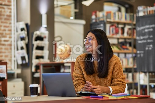 istock young woman studying in the library 1069232558
