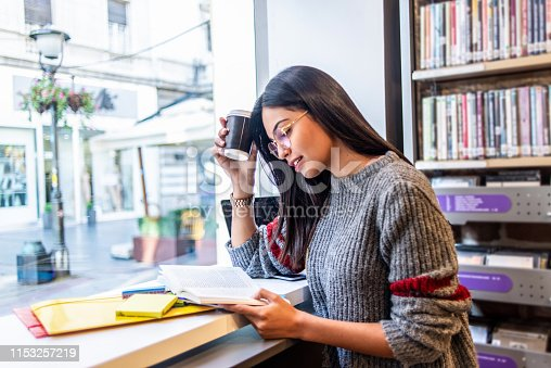 istock young woman studying in the library 1153257219