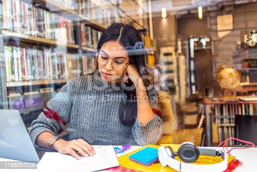 istock young woman studying in the library 1153257220