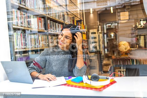 istock young woman studying in the library 1153257268