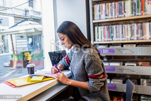 istock young woman studying in the library 1153257403