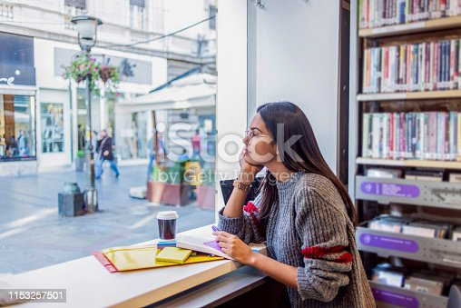 istock young woman studying in the library 1153257501