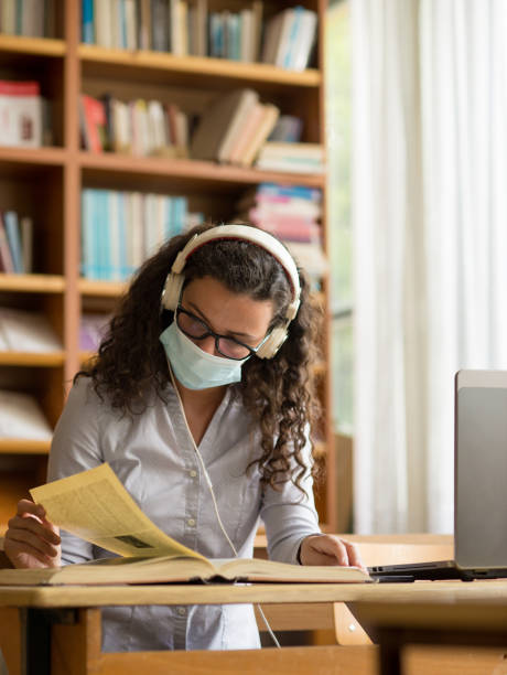 Young woman studying in the library stock photo