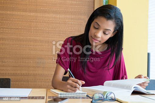 istock Young woman studying in the library 488148586