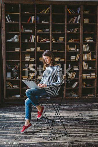 istock Young woman studying in the library 691832446