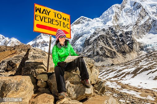 Young woman, wearing green jacket, is sitting and studying map in Himalayas, Signpost
