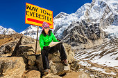 Young woman, wearing green jacket, is sitting and studying map in Himalayas, Signpost \