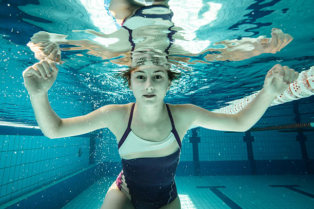 Young woman submerded in a swimming pool stock photo