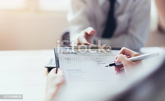 istock Young woman submit resume to employer to review job application. The concept presents the ability for the company to agree with the position of the job. 1010098830